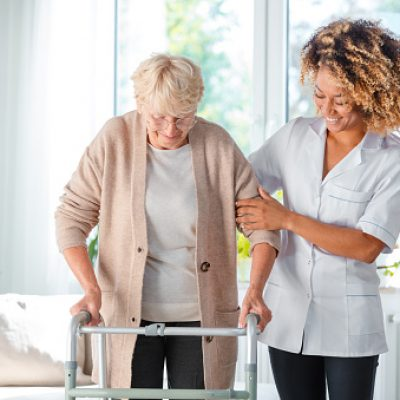Cheerful friendly nurse helping senior woman to use walking frame